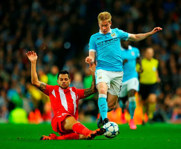 Kevin De Bruyne is tackled by Sevilla's Vitolo