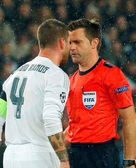 Sergio Ramos reacts to referee Nicola Rizzoli after receiving a yellow card