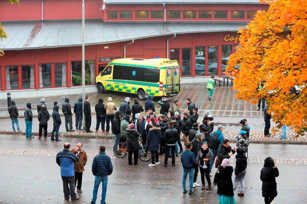 Onlookers stand outside a cordoned area after a masked man attacked people with a sword at a school in Trollhattan, western Sweden October 22, 2015. The masked man wielding a sword killed one person and wounded four at the school in western Sweden before being shot by police, authorities said on Thursday. The incident occurred at the Kronan school in Trollhattan, an industrial town of around 50,000 inhabitants north of Gothenburg. REUTERS/Bjorn Larsson Rosvall/TT News Agency ATTENTION EDITORS - THIS IMAGE WAS PROVIDED BY A THIRD PARTY. FOR EDITORIAL USE ONLY. NOT FOR SALE FOR MARKETING OR ADVERTISING CAMPAIGNS. THIS PICTURE IS DISTRIBUTED EXACTLY AS RECEIVED BY REUTERS, AS A SERVICE TO CLIENTS. SWEDEN OUT. NO COMMERCIAL OR EDITORIAL SALES IN SWEDEN. NO COMMERCIAL SALES.