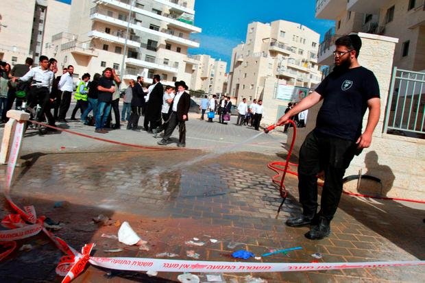 A Jewish man cleans the site where two alleged Palestinian attackers were killed after stabbing an Israeli man Credit: Gil Cohen-Magen (AFP//Getty Images)