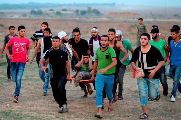 Palestinian protesters carry a comrade who was shot during clashes with Israeli soldiers near the border fence between Israel and the central Gaza Strip Credit: Mohammed Abed (AFP/Getty Images)