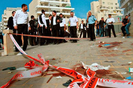 Israeli ultra-orthodox Jews gather at the site where two alleged Palestinian attackers were shot by Israeli police after attempting to board a bus carrying children Credit: Gil Cohen-Magen (AFP//Getty Images)