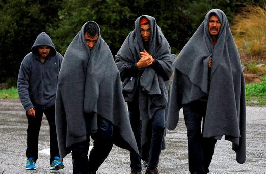 Syrian refugees walk through rain and fog on their way to the nearest registration camp on the Greek island of Lesbos. Photo: Reuters