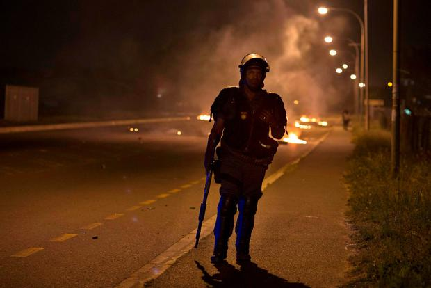 A member of the South African Police Services stands guard close to burning barricades set up by protesting students Credit: Rodger Boscher (AFP)