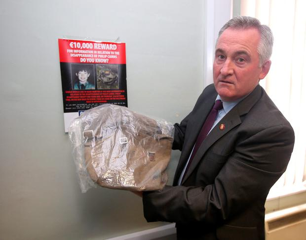 Detective Sergeant, Tom Doyle, of Rathfarnham Garda Station holding the schoolbag belonging to Philip Cairns who has been missing since October 23, 1986. Photo: Damien Eagers