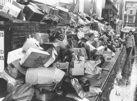 A woman walks past a pavement piled high with rubbish due to a refuse collector's strike, Shepherd Street, Central London, during the 'Winter of Discontent'.