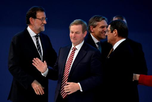 Taoiseach Enda Kenny waves next to Spanish Prime Minister Mariano Rajoy (left) after a family photo at the end of the European People's Party meeting in Madrid. Photo: Getty