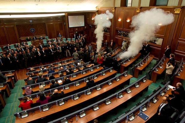 Smoke rises from inside the chamber of parliament as opposition lawmakers disrupt Parliament's session using tear gas, in Pristina, Kosovo (AP Photo/Visar Kryeziu)