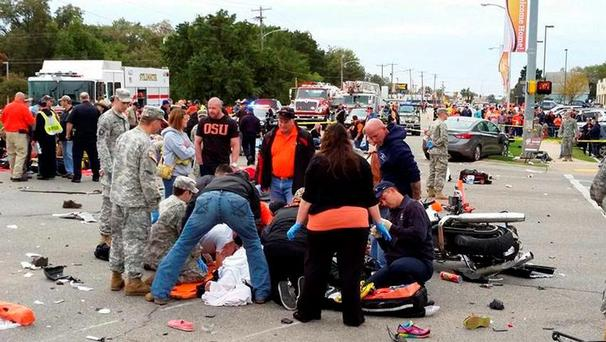 People attend to the injured at the scene of a car crash after a car drove into a homecoming parade at Oklahoma State University in Stillwater, Oklahoma