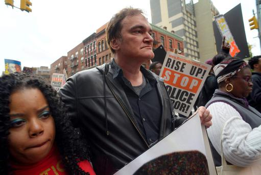Director Quentin Tarantino, center, participates in a rally to protest against police brutality Saturday (AP Photo/Patrick Sison)
