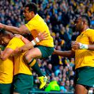 Australia's wing Adam Ashley-Cooper (L) celebrates with teammates after scoring his team's second try during a semi-final match of the 2015 Rugby World Cup between Argentina and Australia at Twickenham Stadium, southwest London, on October 25, 2015. AFP PHOTO / GLYN KIRK