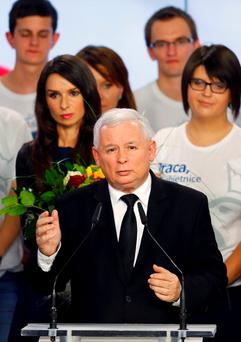 The leader of Poland's main opposition party Law and Justice (PiS) Jaroslaw Kaczynski addresses as his niece Marta (L) looks on after the exit poll results are announced in Warsaw