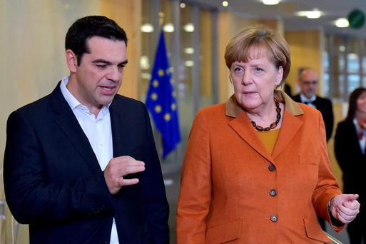 Greece's Alexis Tsipras chats with Germany's Angela Merkel at the meeting over the refugee crisis
