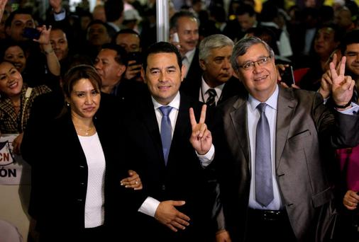 Guatemala's President-elect Jimmy Morales (C), his wife Gilda Marroquin (L) and his running mate Jafeth Cabrera pose for photographs after winning the presidential election in Guatemala City REUTERS/Jose Cabezas