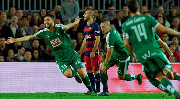 Eibar's forward Borja Gonzalez (L) celebrates next to Barcelona's Argentinian defender Javier Mascherano (C) after scoring a goal during the Spanish league football match FC Barcelona vs SD Eibar at the Camp Nou