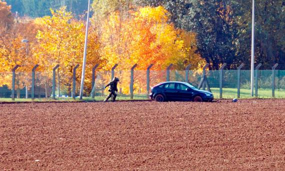 A member of the bomb squad investigates a suspect car parked in a field outside a military barracks in Flawinne, Belgium (AP Photo/Virginia Mayo)