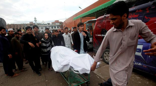 A man wheels a body of a woman, who died in an earthquake, at the Lady Reading hospital, Peshawar, Pakistan REUTERS/Fayaz Aziz