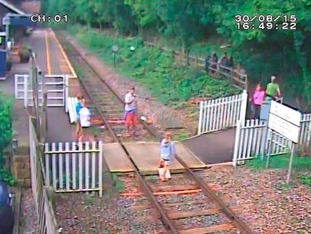 Man taking a picture of a child on the track at Matlock Bath station in Derbyshire, one of the eight dangerous incidents captured by CCTV at the level crossing in a single day, as people have been warned not to take selfies on train tracks Credit: Network Rail/PA Wire