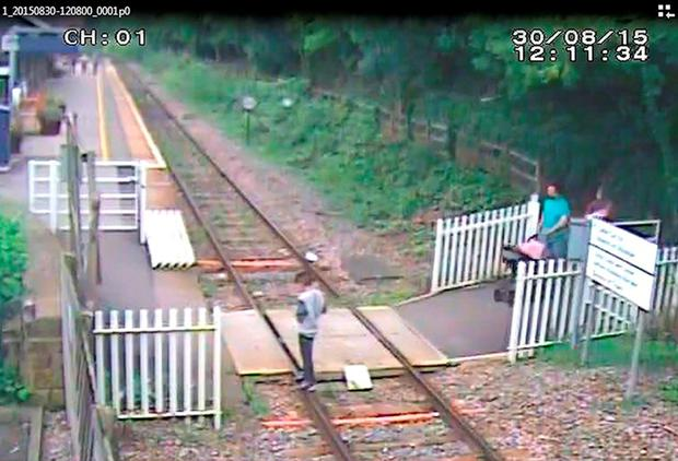 Boy texting on his phone while standing on the track at Matlock Bath station in Derbyshire Credit: Network Rail/PA Wire