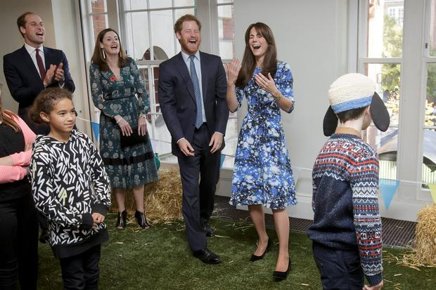 Prince William, Duke of Cambridge, left, Prince Harry, centre, and Catherine, Duchess of Cambridge, right, smile as they take part in 'welly wanging'