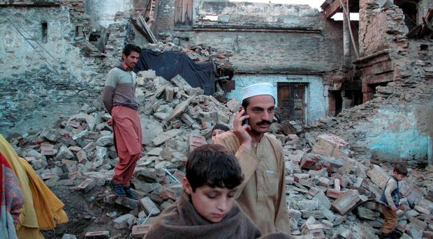 Residents walk past the rubble of a house after it was damaged by an earthquake in Mingora, Swat, Pakistan. REUTERS/Hazrat Ali Bacha