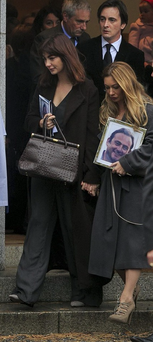 Sisters Chloe and Leigh Arnold, carrying a photo of Nicky, leave the church in Carrickmines