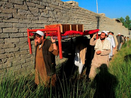 Afghan men carry a coffin of an earthquake victim for burial in Behsud district of Nangarhar province, Afghanistan October 27, 2015