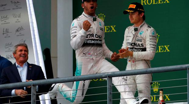 Mercedes Formula One driver Lewis Hamilton of Britain celebrates after winning the U.S. F1 Grand Prix as teammate Nico Rosberg of Germany applauds at the Circuit of The Americas in Austin