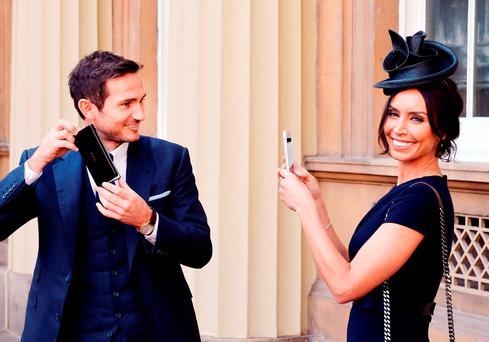 Frank Lampard with partner Christine Bleakley as he holds his Officer of Order of the British Empire (OBE) medal, after it was presented to him by the Duke of Cambridge, at an Investiture ceremony at Buckingham Palace in central London
