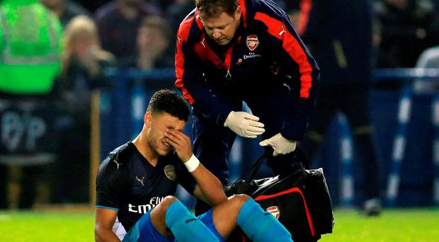 Arsenal's Alex Oxlade-Chamberlain dejected with the physio as he sits injured during the Capital One Cup, fourth round match at Hillsborough