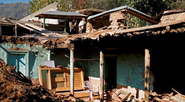 A man walks on the roof of a house damaged by earthquake in the village of Aryankoat near Dir Bala, Pakistan October 28, 2015