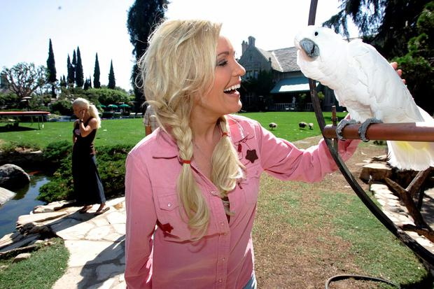 Bridget, one of the three girlfriends of Playboy Enterprises CEO Hugh Hefner plays with animals of Hefner's private zoo during a guided tour of the mansion in Los Angeles, CA 23 August 2006.