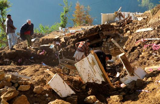 Pakistani villagers collect their belongings under the rubble of their homes destroyed from an earthquake in Shangla in Swat valley, Pakistan. (AP Photo/Naveed Ali)
