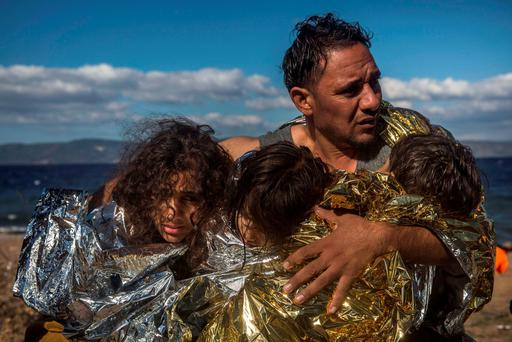 A man holds three children wearing thermal blankets after their arrival in bad weather from Turkey on the Greek island of Lesbos (AP Photo/Santi Palacios)