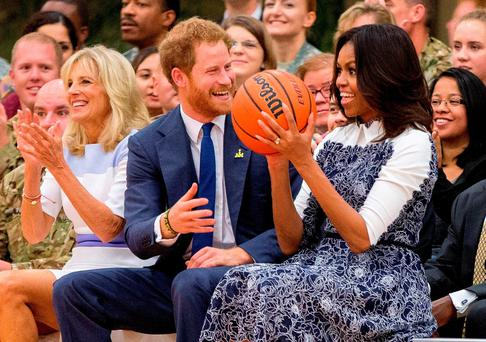 First lady Michelle Obama, accompanied by Jill Biden, left, reacts as Britain's Prince Harry hands her the basketball as the conclusion of a game of wheelchair basketball by wounded servicemen and veterans at Fort Belvoir military base (AP Photo/Andrew Harnik)
