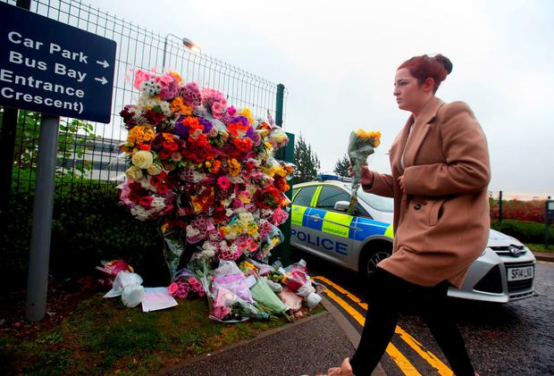 Floral tributes are left outside Cults Academy in Aberdeen, as police continue to question a teenager after a 16-year-old boy died in a stabbing at the secondary school