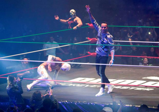 Mexican lucha libre wrestler Mistico kneels as 2015 Formula One champion and Mercedes team driver Lewis Hamilton raises his arm during a