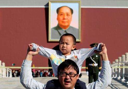 A boy sits on his father's shoulders as they pose for a photograph in front of the giant portrait of late Chinese chairman Mao Zedong on the Tiananmen Gate, in Beijing, China Photo: Reuters/Stringer
