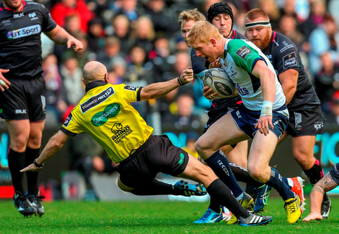 Referee Andrew Brace is bowled over as Connacht's Darragh Leader escapes the tackle of Dan Baker of Ospreys