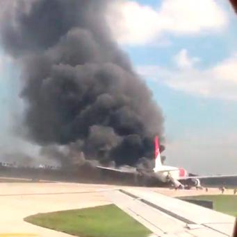A still image from a handout video footage by Mike Dupuy, a passenger in another airplane, shows Dynamic International Airways' Boeing 767's engine on fire in Fort Lauderdale. Photo: Reuters