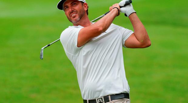 Scott Piercy of the US watches his shot on the 18th hole