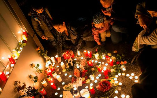 People light candles during a solemn vigil for a killed boy at the gate of the Berlin Office of Health and Social Affairs (LAGESO) in Berlin, Germany REUTERS/Hannibal Hanschke