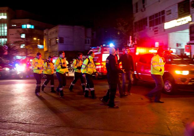 Emergency workers walk outside the scene of an explosion that occurred in a club in Bucharest (AP Photo/Vadim Ghirda)