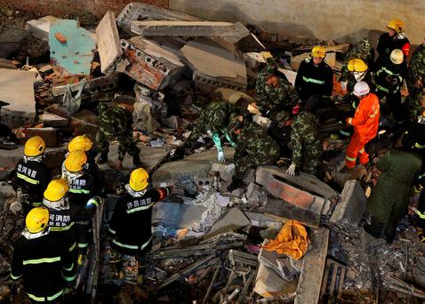 Rescuers search for survivors among debris after a residential building collapsed in Wuyang county, Henan province, China REUTERS/Stringer
