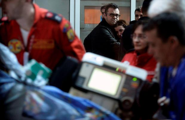 A couple hug as a person injured during a fire at a nightclub is carried on a stretcher at the emergency hospital in Bucharest, Romania October 31, 2015. A fire in a Bucharest nightclub killed 27 people and injured 184 during a rock concert that featured fireworks late on Friday, Romanian government officials and witnesses said. In one of the capital's worst disasters in decades, about 400 people, mostly young adults, stampeded for the only available exit as the club in the basement of a Communist-era sport-shoe factory filled with smoke. REUTERS/Inquam Photos/Octav Ganea THIS IMAGE HAS BEEN SUPPLIED BY A THIRD PARTY. IT IS DISTRIBUTED, EXACTLY AS RECEIVED BY REUTERS, AS A SERVICE TO CLIENTS. ROMANIA OUT. NO COMMERCIAL OR EDITORIAL SALES IN ROMANIA.