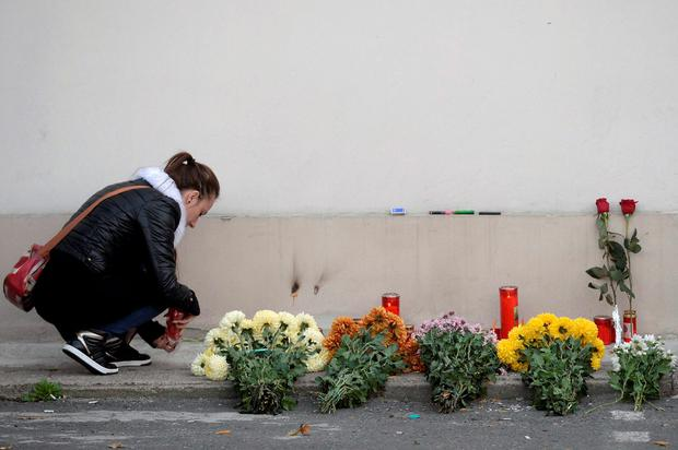 A woman lights a candle outside a nightclub, where a fire broke out on Friday, in Bucharest, Romania October 31, 2015. The fire in the nightclub killed 27 people and injured 184 during a rock concert that featured fireworks, Romanian government officials and witnesses said. In one of the capital's worst disasters in decades, about 400 people, mostly young adults, stampeded for the only available exit as the club in the basement of a Communist-era sport-shoe factory filled with smoke. REUTERS/Inquam Photos/Octav Ganea THIS IMAGE HAS BEEN SUPPLIED BY A THIRD PARTY. IT IS DISTRIBUTED, EXACTLY AS RECEIVED BY REUTERS, AS A SERVICE TO CLIENTS. ROMANIA OUT. NO COMMERCIAL OR EDITORIAL SALES IN ROMANIA.