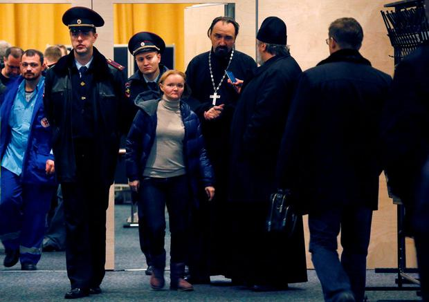 Police officers control the situation as relatives and the friends of those on the Metrojet flight that crashed in Egypt gather to grieve at a hotel near St. Petersburg's Pulkovo airport outside St.Petersburg, Russia, Saturday, Oct. 31, 2015. (AP Photo/Dmitry Lovetsky)