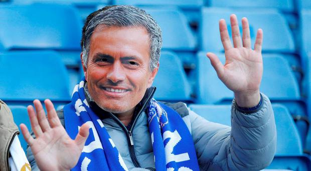 A supporters wearing a Jose Mourinho mask waves from his seat ahead of the English Premier League football match between Chelsea and Liverpool at Stamford Bridge