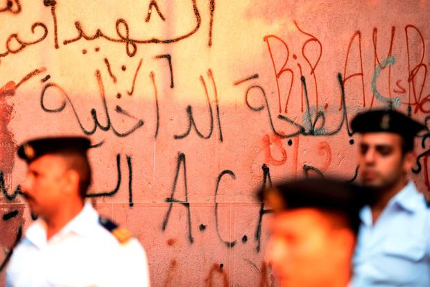 Egyptian police officers stand guard, next to graffiti condemning police brutality, outside the Zeinhom Morgue in Cairo on October 31, 2015, as they wait for the victims of the Russian charter plane. AFP PHOTO /MOHAMED EL-SHAHEDMOHAMED EL-SHAHED/AFP/Getty Images