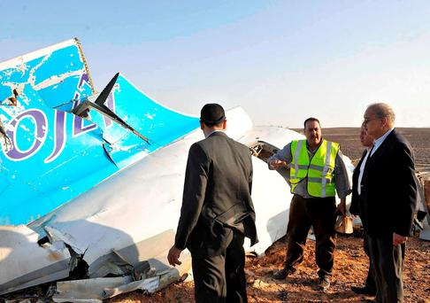 In this image released by the Prime Minister's office, Sherif Ismail, right, looks at the remains of a crashed passenger jet in Hassana Egypt, Friday, Oct. 31, 2015. (Suliman el-Oteify, Egypt Prime Minister's Office via AP)